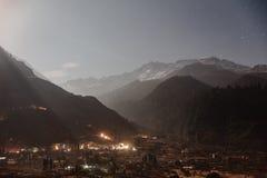 Montaña con poca nieve en el top con el pueblo encendido abajo en la noche del invierno en Lachung en Sikkim del norte, la India Fotos de archivo libres de regalías