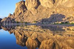 Montaña con reflexiones en un río, oasis de Fint. Imagen de archivo libre de regalías