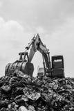 Montaña de la basura con la retroexcavadora de trabajo Imagen de archivo libre de regalías