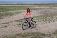 Montaña de la mujer biking en tierra de la arena Foto de archivo