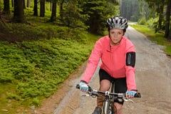 Montaña de la mujer biking a través del camino forestal fotografía de archivo
