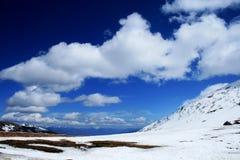 Montaña de la nieve, cielo azul y nube blanca foto de archivo