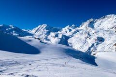 Montaña de la nieve, pista del esquí, huellas en nieve con el poste indicador minúsculo Fotografía de archivo