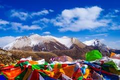 Montaña de la nieve y las banderas del rezo en Tíbet Imágenes de archivo libres de regalías