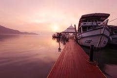 Montaña de la puesta del sol al lado del barco Imagen de archivo libre de regalías