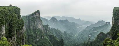 Montaña de Tianmen conocida como la puerta del ` s del cielo rodeada por el bosque y la niebla verdes en Zhangjiagie, provincia d foto de archivo libre de regalías