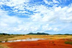 Montaña de tierra roja y cielo azul Imagen de archivo