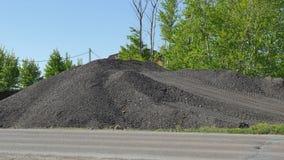 Montaña del asfalto quebrado cerca del camino Foto de archivo libre de regalías