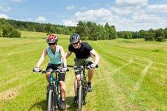 Montaña del deporte biking - hombre que empuja a la chica joven Imagenes de archivo