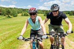 Montaña del deporte biking - hombre que empuja a la chica joven Imágenes de archivo libres de regalías