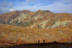 Montaña del otoño coloreada a la naranja y a las siluetas de la gente fotografía de archivo libre de regalías
