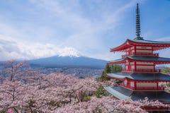 Montaña Fujiyama, una marca de tierra notable de Japón en un día nublado con la flor de cerezo o Sakura en el marco La imagen de  Foto de archivo