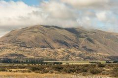 Montaña grande en nubes en la roca media de la tierra, Nueva Zelanda Imagenes de archivo