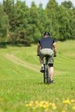 Montaña juguetona del hombre biking prados asoleados Fotografía de archivo libre de regalías