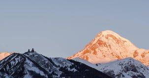 Montaña Kazbek del invierno con nieve, e iglesia vieja Amanecer de la salida del sol almacen de metraje de vídeo