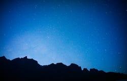 montaña negra con el cielo azul, estrellas llenas Fotografía de archivo libre de regalías