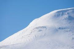 Montañas nevosas hermosas con el cielo azul en el fondo Fotografía de archivo
