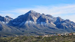 Montaña nevada que se eleva sobre un valle verde, verde fotografía de archivo libre de regalías