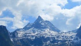 Montaña nevosa grande agradable y nubes blancas Fotografía de archivo libre de regalías