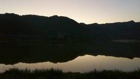 Montaña por el lago en amanecer con el cielo colorido imágenes de archivo libres de regalías