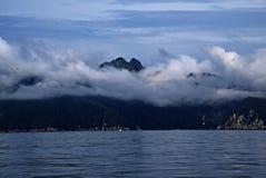 Montaña que mira a escondidas a través de las nubes Imagenes de archivo