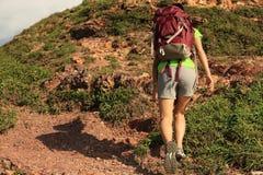 Montaña que sube del backpacker de la mujer joven imagen de archivo libre de regalías