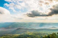 Montaña verde cubierta por el cielo nublado Fotografía de archivo