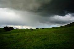 Montaña verde debajo de la nube pesada Foto de archivo