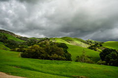 Montaña verde debajo de la nube pesada Fotos de archivo