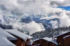 Montañas alpinas en las nubes en invierno Imagen de archivo libre de regalías