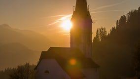 Montañas anaranjadas Suiza 4k aéreo de la iglesia de la puesta del sol almacen de metraje de vídeo