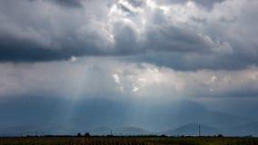 Montañas brumosas más allá del llanos planos bañados en rayos del sol foto de archivo libre de regalías