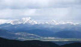 Montañas capsuladas nieve cubiertas en nubes de tormenta Imágenes de archivo libres de regalías