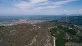 Montañas con el pequeños camino y ciudad Imagen de archivo libre de regalías