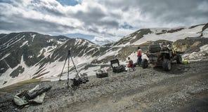 Montañas con errores que conducen en el camino con extremo de la nieve imagenes de archivo