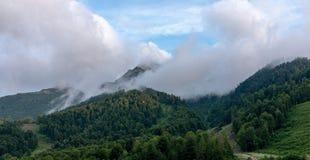 Montañas con las cuestas verdes y teleféricos en niebla densa imagen de archivo