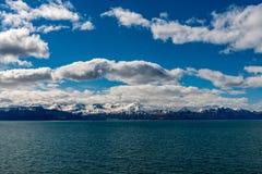 Montañas con los cielos azules de las nubes, agua en frente Foto de archivo libre de regalías