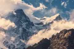 Montañas con los picos nevosos en nubes en la puesta del sol Imágenes de archivo libres de regalías