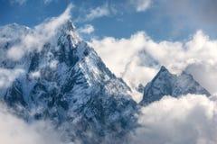 Montañas con los picos nevosos en nubes en Nepal Foto de archivo libre de regalías