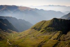 Montañas con niebla, el valle y el río Foto de archivo