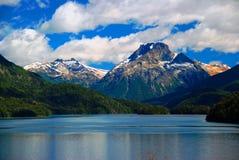 Montañas con nieve sobre el lago azul Foto de archivo