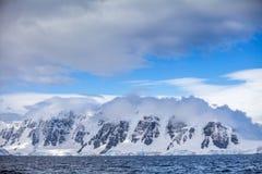 Montañas coronadas de nieve hermosas de la Antártida de los paisajes contra el cielo azul Imágenes de archivo libres de regalías