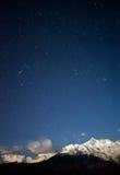 Montañas coronadas de nieve y las estrellas imagenes de archivo