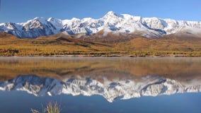 Montañas coronadas de nieve y un lago en el llano abajo almacen de metraje de vídeo