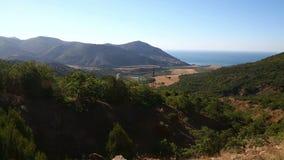 Montañas cubiertas con la vegetación verde que pasa por alto el mar almacen de metraje de vídeo