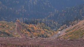 Montañas cubiertas con los árboles del otoño, camino del cable con la telesilla almacen de video