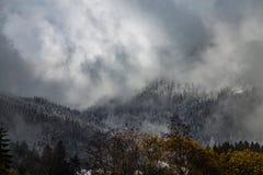 Montañas cubiertas con nieve y rodeadas por las nubes imagen de archivo