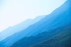 Montañas cubiertas en niebla azulada Imagenes de archivo