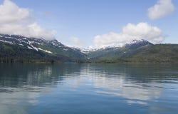 Montañas de Alaska sobre el agua tranquila Fotos de archivo libres de regalías