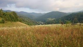 Montañas de la casa del pueblo de la hierba del aire Foto de archivo libre de regalías
